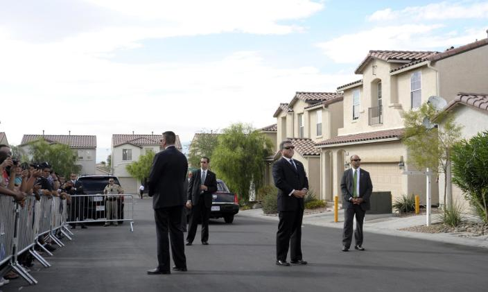 FILE - In this Monday, Oct. 24, 2011 file photo, Secret Service agents stand guard as President Barack Obama meets with the neighbors of homeowners Jose and Lissette Bonilla in Las Vegas. The Secret Service has been tarnished by a prostitution scandal that erupted April 13, 2012 in Colombia involving 12 Secret Service agents, officers and supervisors and 12 more enlisted military personnel ahead of President Barack Obama's visit there for the Summit of the Americas. (AP Photo/Susan Walsh)