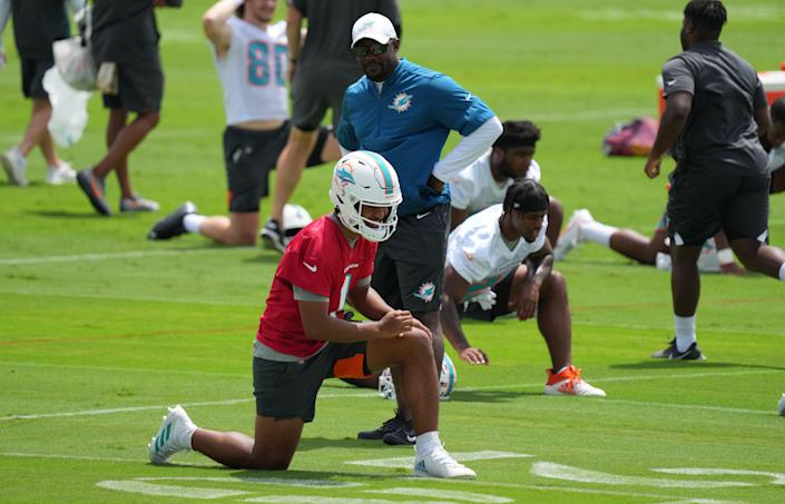 Quarterback Tua Tagovailoa #1 of the Miami Dolphins interacts with head coach Brian Flores while stretching prior to the start of Mandatory Minicamp at Baptist Health Training Facility at Nova Southern University on June 15, 2021 in Miami, Florida.