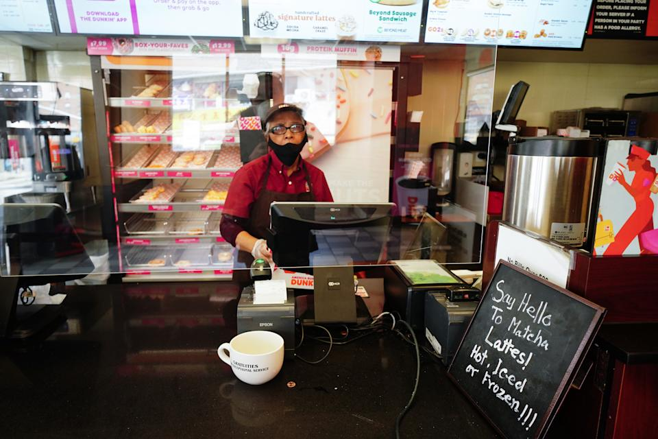 A view of a Dunkin' Donuts cashier protected by a plastic partition as anti-COVID-19 measure in Flushing Queens New York USA during coronavirus pandemic on April 16, 2020.  (Photo by John Nacion/NurPhoto via Getty Images)