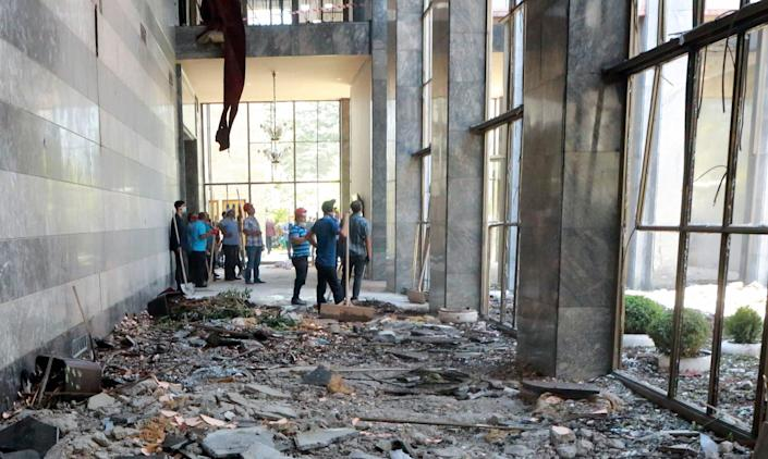 Workers inspect and clear debris at the Grand National Assembly.