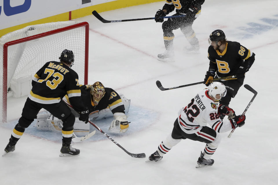 Chicago Blackhawks center Ryan Carpenter (22) starts to celebrate his goal against Boston Bruins goaltender Tuukka Rask (40) as Bruins defenseman Charlie McAvoy (73) and Bruins right wing David Pastrnak (88) look on in the first period of an NHL hockey game, Thursday, Dec. 5, 2019, in Boston. (AP Photo/Elise Amendola)