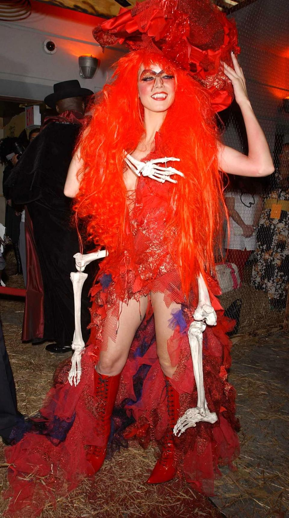 <p>In 2004, Klum went as a scary/sexy red witch with a skeleton stowaway. (Photo: Getty Images) </p>