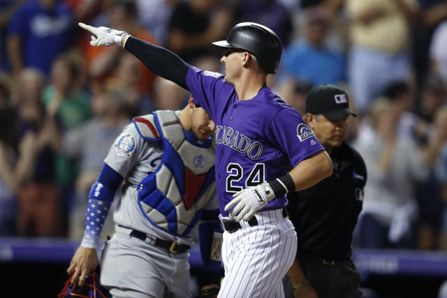 Colorado Rockies' Ryan McMahon, front, gestures as he crosses home plate after hitting a two-run home run, next to Los Angeles Dodgers catcher Yasmani Grandal during the seventh inning of a baseball game Friday, Aug. 10, 2018, in Denver. (AP Photo/David Zalubowski)