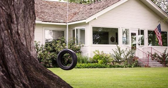 Tire swing in front of home | Hill Street Studios/Getty Images
