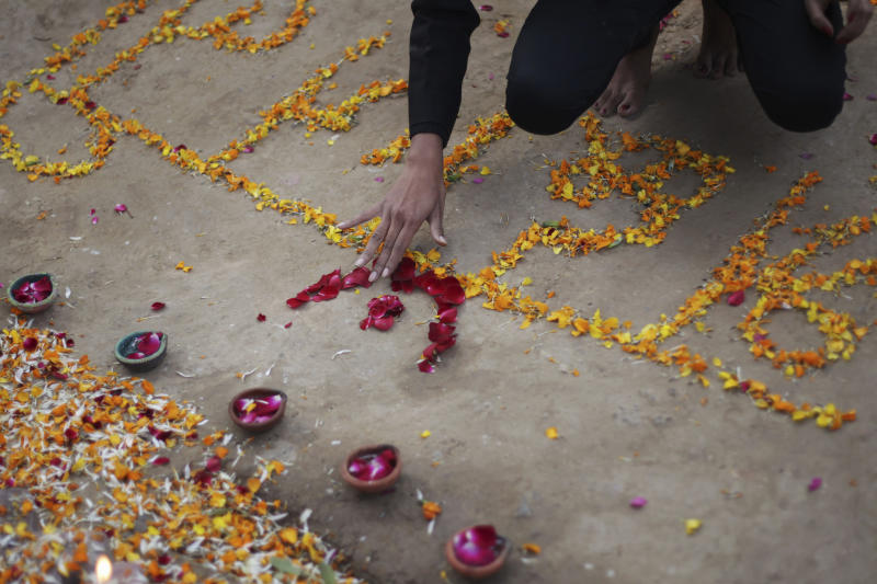 """An Indian woman places flowers on the floor reading """"Condolence to Damini,"""" a symbolic name given to a gang rape victim, in New Delhi, India, Monday, Dec. 16, 2013. The victim, a 23-year-old physiotherapy student, became a rallying cry for tens of thousands protesting the treatment of women. In some ways, the case cracked a cultural taboo surrounding discussion of sexual violence in a country where rape is often viewed as a woman's personal shame to bear. (AP Photo/Tsering Topgyal)"""