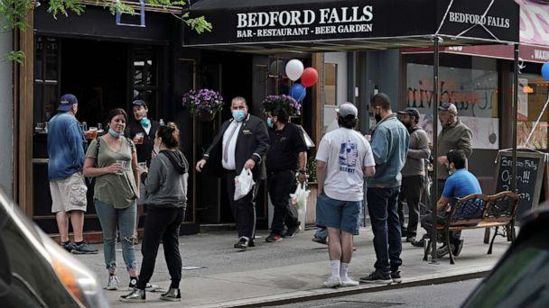 PHOTO: People gather outside a bar selling to-go drinks during the coronavirus pandemic on May 18, 2020 in New York City. (Cindy Ord/Getty Images)