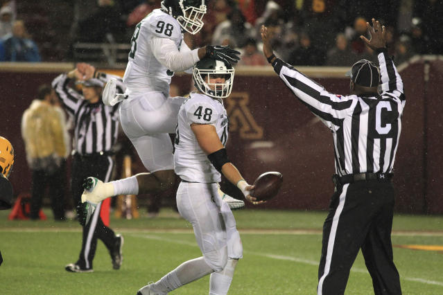 Michigan State Kenny Willekes (48) tosses the ball to an official after recovering a fumble as teammate Demetrius Cooper (98) comes in to celebrate, Saturday, Oct. 14, 2017, in Minneapolis. (AP Photo/Andy Clayton-King)