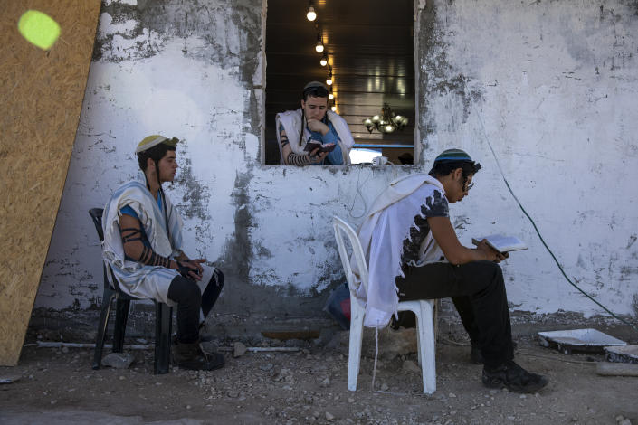 Israeli settlers pray in a synagogue at the recently established wildcat Jewish outpost of Eviatar, near the northern Palestinian West Bank town of Nablus, Monday, June 28, 2021. Palestinians say the outpost was established on private farmland. Israeli media said Monday that the government was working on reaching a compromise with the settlers that would see the outpost evacuated in the coming days. (AP Photo/Ariel Schalit)