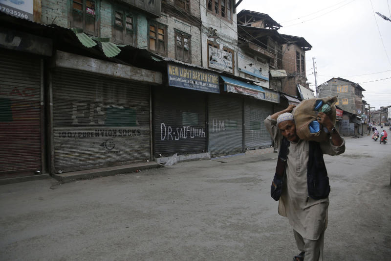 An elderly Kashmiri man selling sandals walks through a closed market in Srinagar, Indian controlled Kashmir, Wednesday, Aug. 28, 2019. India's government, led by the Hindu nationalist Bharatiya Janata Party, imposed a security lockdown and communications blackout in Muslim-majority Kashmir to avoid a violent reaction to the Aug. 5 decision to downgrade the region's autonomy. The restrictions have been eased slowly, with some businesses reopening, some landline phone service restored and some grade schools holding classes again, though student and teacher attendance has been sparse. (AP Photo/Mukhtar Khan)
