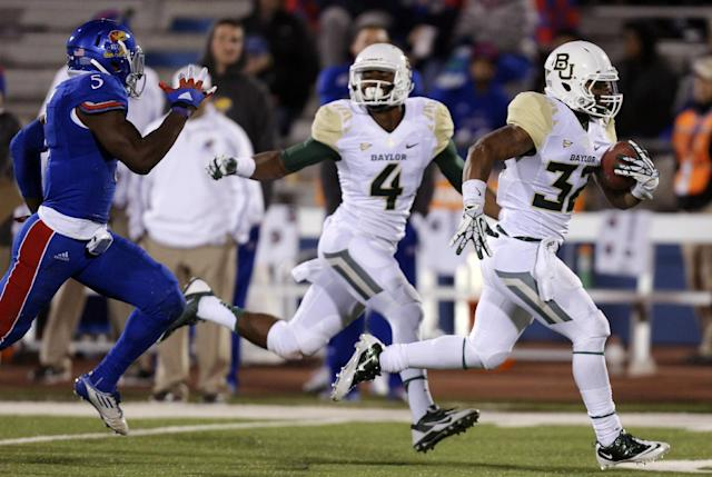 Baylor Bears running back Shock Linwood (32) runs past Kansas Jayhawks safety Isaiah Johnson (5) for a touchdown run in the fourth quarter of an NCAA college football game Saturday, Oct. 26, 2013, in Lawrence, Kan. Baylor won 59-14. (AP Photo/Ed Zurga)