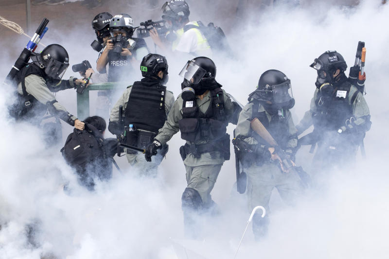 Police in riot gear move through a cloud of smoke as they detain a protester at the Hong Kong Polytechnic University in Hong Kong, Nov. 18, 2019. (Photo: Ng Han Guan/AP)