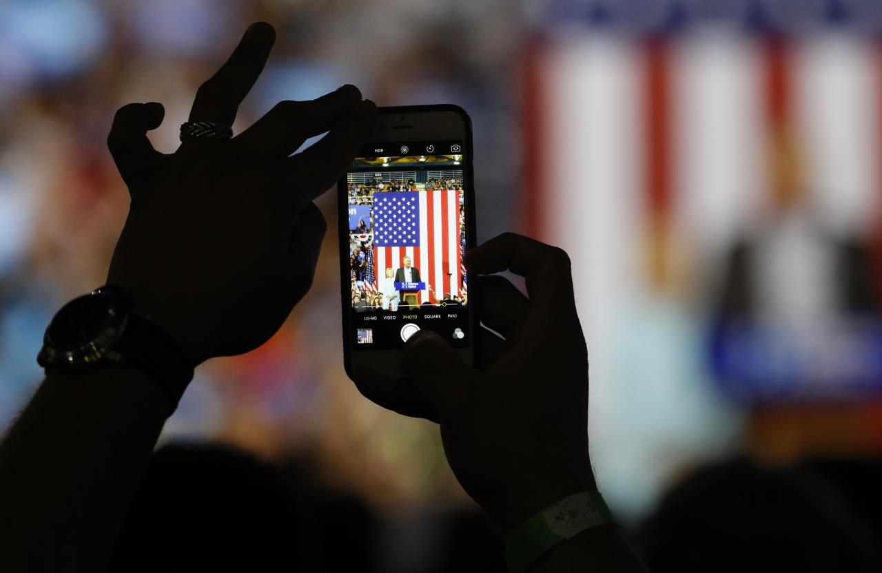 An attendee shoots a photo on a cell phone of Democratic U.S vice presidential candidate Senator Tim Kaine (D-VA) speaking as he appears with Democratic U.S. presidential candidate Hillary Clinton during a campaign rally in Miami, Florida, U.S. July 23, 2016.  REUTERS/Scott Audette  TPX IMAGES OF THE DAY