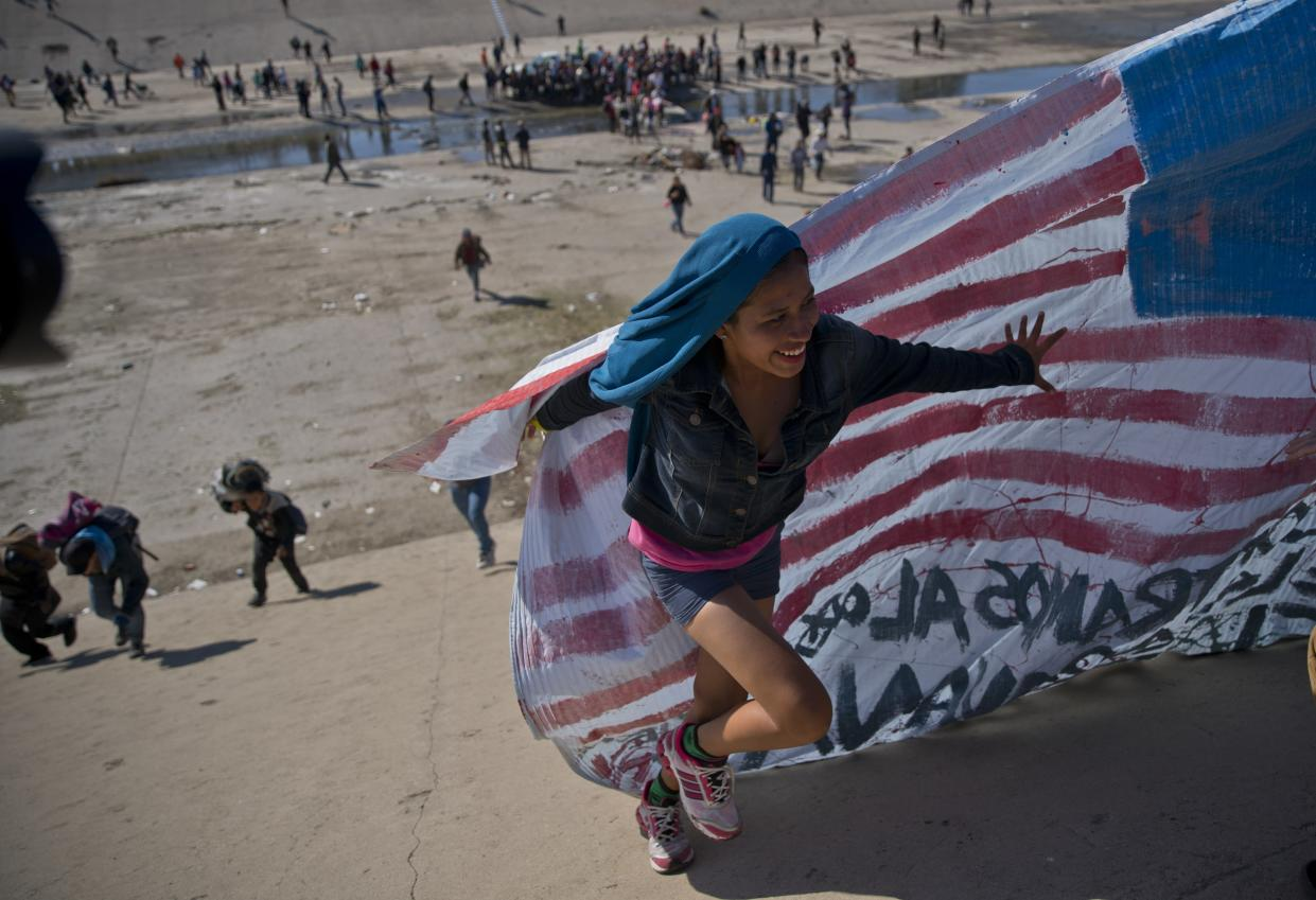 A migrant woman helps carry a handmade U.S. flag up the riverbank at the Mexico-U.S. border after getting past Mexican police at the Chaparral border crossing in Tijuana, Mexico, Sunday, Nov. 25, 2018, as a group of migrants tries to reach the U.S. (Photo: Ramon Espinosa/AP)