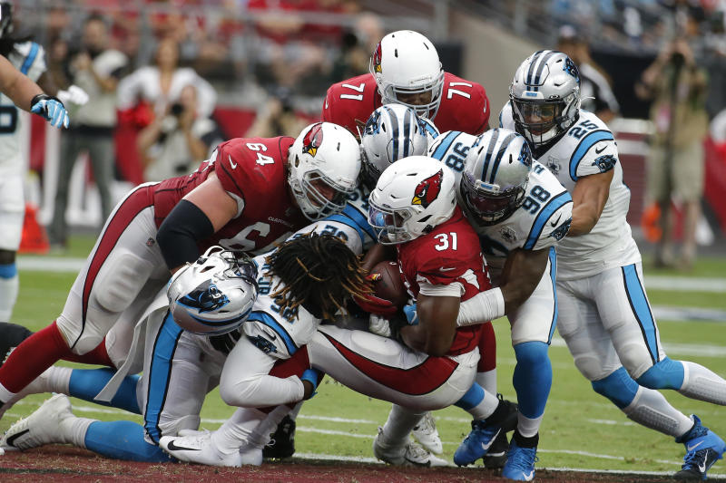 """FILE - In this Sunday, Sept. 22, 2019, file photo, Arizona Cardinals' David Johnson (31) is stopped by the Carolina Panthers defense during an NFL football game in Glendale, Ariz.  You can take that """"any given Sunday"""" bromide and toss it out with some of Case Keenum's interceptions. So far in 2019, there is a Grand Canyon of separation between the contenders and everybody else. (AP Photo/Rick Scuteri, File)"""