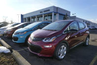 A 2021 Chevrolet Bolt EV, is displayed with 2020 models at Bill Crispin Chevrolet Thursday, Feb. 25, 2021, in Saline, Mich. Opinion polls show that most Americans would consider an EV if it cost less, there were more charging stations along freeways, and if automakers offered a bigger variety of models. (AP Photo/Carlos Osorio)