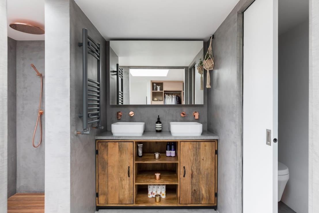 """<p>Modern? Industrial? How about rustic? It doesn't matter which style this<a rel=""""nofollow"""" href=""""https://www.homify.co.uk/rooms/bathroom"""">bathroom</a> flaunts, we can all agree that it's quite stunning! An elegant grey adorns the walls, making the wooden and copper finishes become all the more prominent. And of course a firm dose of functionality is also included, as we can see by the bathroom cabinetry looking ripe and ready to help out with a myriad of bathroom goodie storage.</p>  Credits: homify / R+L Architect"""