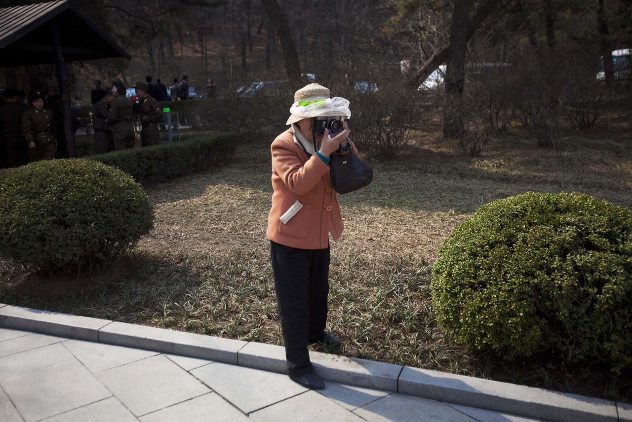 In this April 13, 2011 photo, a professional photographer takes a souvenir picture for visitors to the birthplace of Kim Il Sung at Mangyongdae, North Korea. (AP Photo/David Guttenfelder)