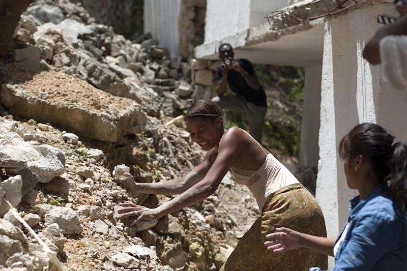 """Nigerian-German singer-songwriter Ayo, center, makes her way around rubble during the filming of """"Murder in Pacot"""" at a home that was damaged in real life by the 2010 earthquake in Port-au-Prince, Haiti, Friday, April 11, 2014. Haiti's most respected filmmaker, Raoul Peck, began production on a new film in Haiti this week, making perhaps the first feature to dramatize how people faced the days and weeks after the 2010 earthquake. (AP Photo/Dieu Nalio Chery)"""
