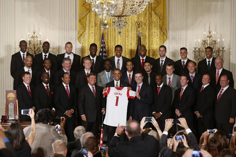 President Barack Obama holds up a Louisville basketball jersey presented to him by coach Rick Pitino, next to the president, right, as he honored the 2013 NCAA Men's Basketball Champions Louisville Cardinals, Tuesday, July 23, 2013, in the East Room at the White House in Washington. (AP Photo/Charles Dharapak)