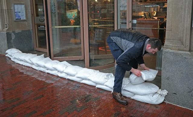 <p>Ryan Adams of JAL Properties management company stacks sandbags at the entrance of 255 State Street in Boston in anticipation of flooding from a nor'easter storm on March 2, 2018. (Photo: David L. Ryan/The Boston Globe via Getty Images) </p>