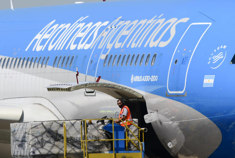 A worker unloads the first shipment of Russia's Sputnik V COVID-19 vaccine from an airplane at the international airport in Buenos Aires, Argentina, Thursday, Dec. 24, 2020. (AP Photo/Gustavo Garello)