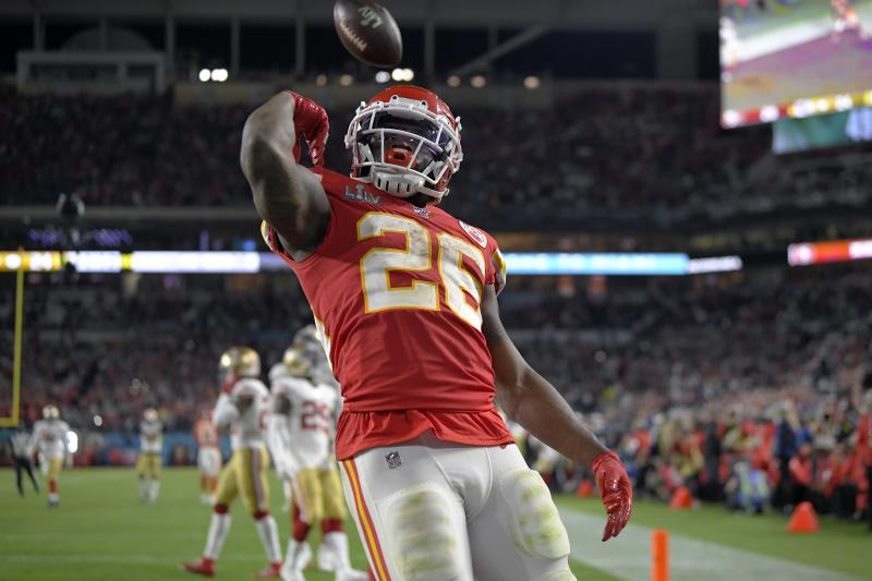 Damien Williams flexes after flipping the football over his head while wearing a red Chiefs uniform.