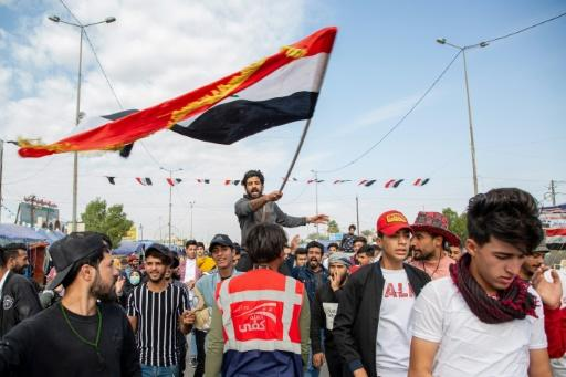 An Iraqi student waves the national flag during anti-government demonstrations in the southern city of Basra