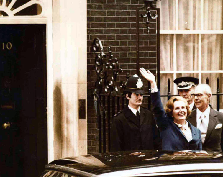 FILE - In this May 4, 1979 file photo, Britain's Conservative Party leader Margaret Thatcher waves to wellwishers as she arrives at 10 Downing Street, London with her husband Denis, right. Thatcher led her party to victory in the General Election and was asked to form a new government.  Britain is facing the most testing and significant, some would say tortuous, period in its modern history since World War II. The polarized electorate now has a critical choice to make _but it seems unlikely the result, whatever it may be, will heal deep and toxic divisions that could last a generation or more. (AP Photo/Bob Dear, File)