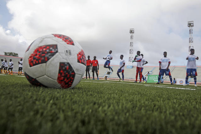 Football players warm up during the reopening of the stadium in Mogadishu, Somalia Tuesday, June 30, 2020. At least three mortar blasts struck the Mogadishu Stadium Tuesday evening, just hours after it was reopened by Somalia's President Mohamed Abdullahi Mohamed, who had left before the shells hit, following years of instability. (AP Photo/Farah Abdi Warsameh)