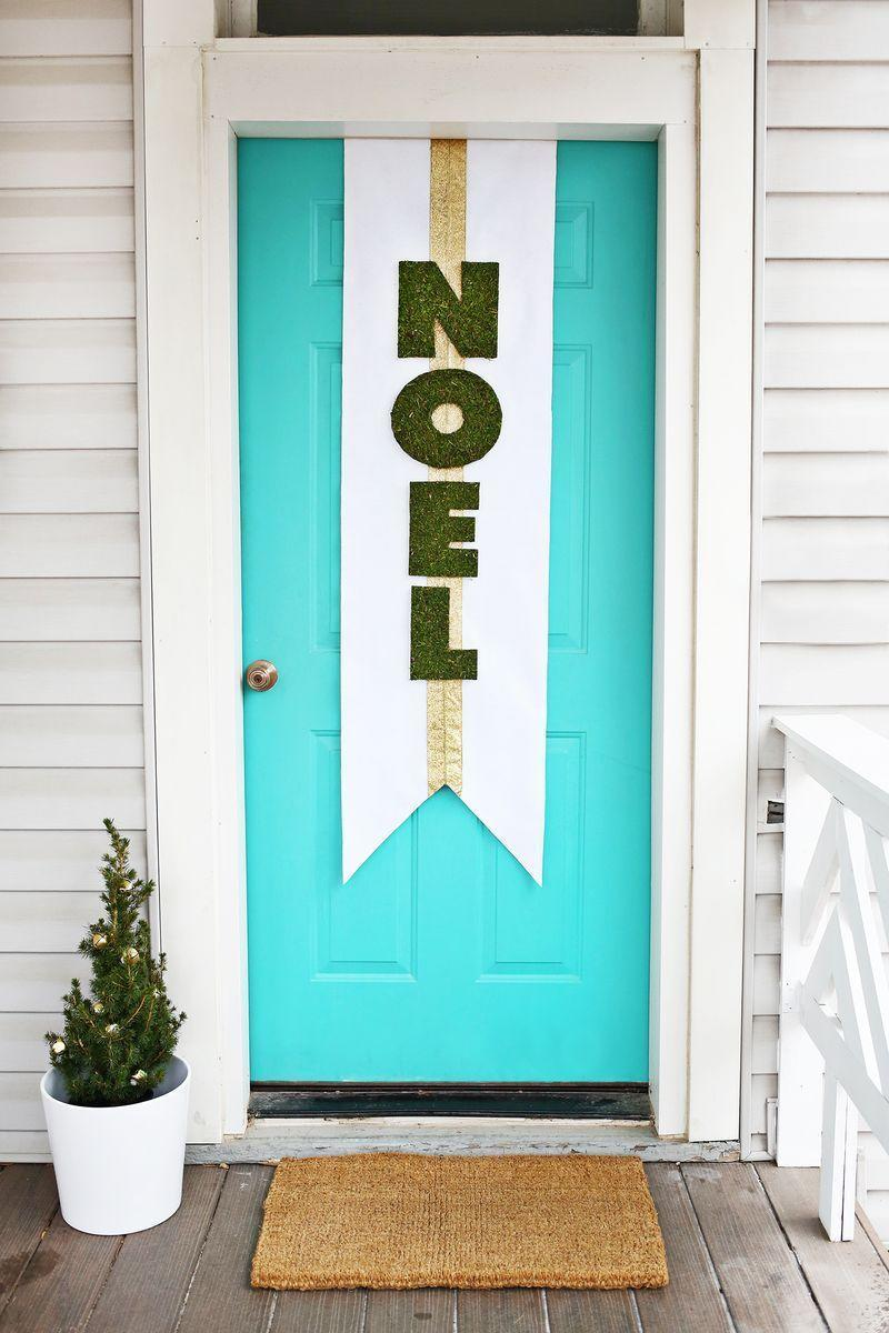 """<p>Make your front door the centerpiece of a stunning Christmas porch with a holiday banner that spans top to bottom. DIY the festive project with some sheet moss, gold ribbon, and cardboard or foam core.<br></p><p><strong><em>Get the look at <a href=""""https://abeautifulmess.com/holiday-door-banner-diy/"""" rel=""""nofollow noopener"""" target=""""_blank"""" data-ylk=""""slk:A Beautiful Mess"""" class=""""link rapid-noclick-resp"""">A Beautiful Mess</a>.</em></strong> </p>"""
