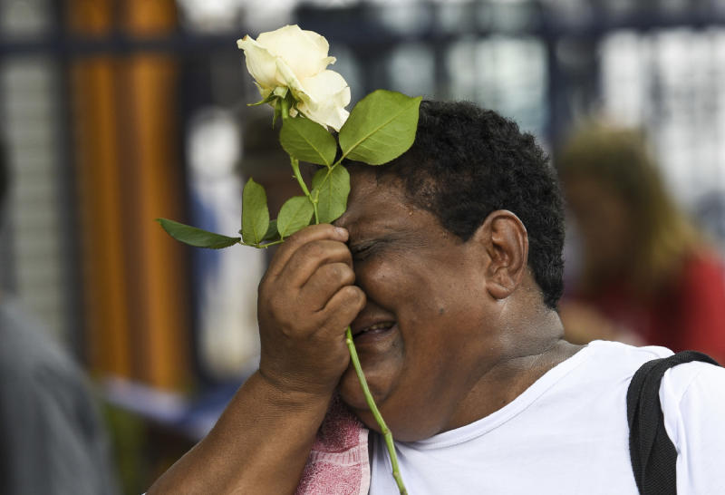 A relative of a victim cries during a tribute to those who died in the dam disaster last year in Brumadinho city, Minas Gerais state, Brazil, Saturday, Jan.25, 2020. The wave of mud and debris that on Jan. 25, 2019 buried the equivalent of 300 soccer pitches and killed 270 people, continues to barrel over residents' minds, the local economy and the environment, one year later. (AP Photo/Gustavo Andrade)