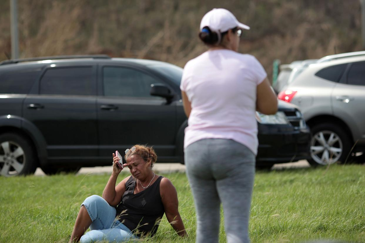 People stop on a highway near a mobile phone antenna tower to check for mobile phone signal, after the area was hit by Hurricane Maria, in Dorado, Puerto Rico September 22, 2017. Picture taken September 22, 2017. REUTERS/Alvin Baez