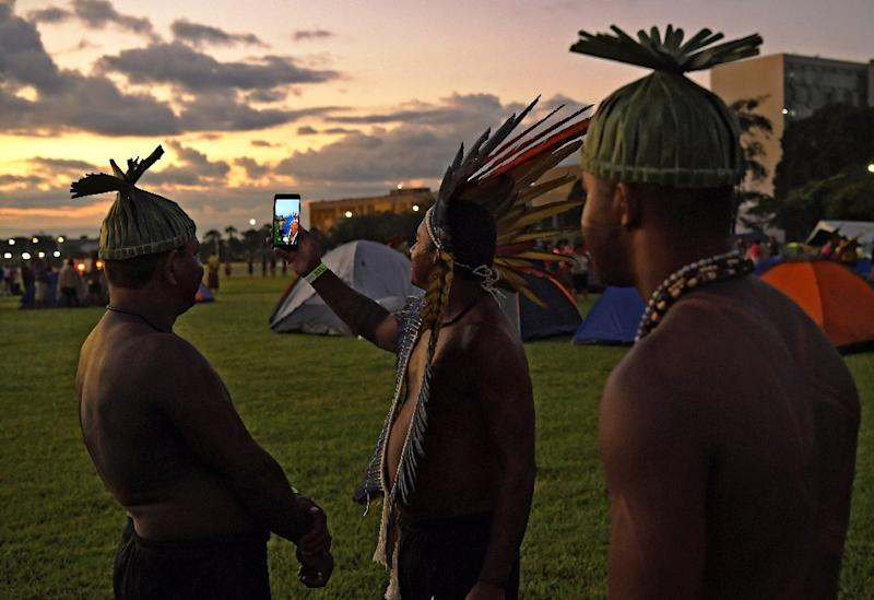 An indigenous man takes a selfie with others during a protest by thousands in defense of land rights outside the National Congress building in Brasilia, Brazil (AFP Photo/CARL DE SOUZA)