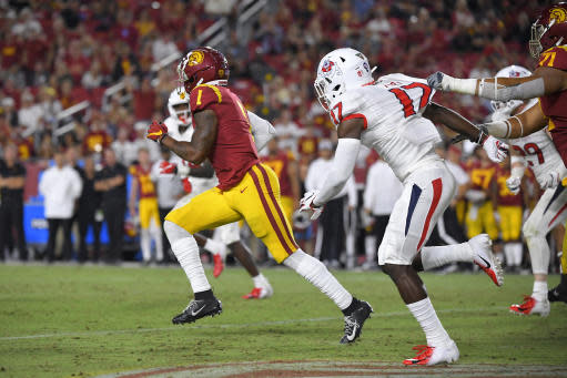 FILE - In this Aug. 31, 2019, file photo, Southern California's Velus Jones Jr., left, runs back a punt for 101 yards as Fresno State's Deonte Perry, second from right gives chase and Liam Jimmons delays Perry during the second half of an NCAA college football game in Los Angeles. Jones is off to a fast start in what is shaping up to be his most productive season as a return specialist. He is averaging 25.6 yards per kick return despite an uncommonly high number of attempts. At a time when most teams seem content to take a touchback, Jones leads the FBS with 3.8 returns per game, one of three players averaging at least three returns per game. (AP Photo/Mark J. Terrill, File)