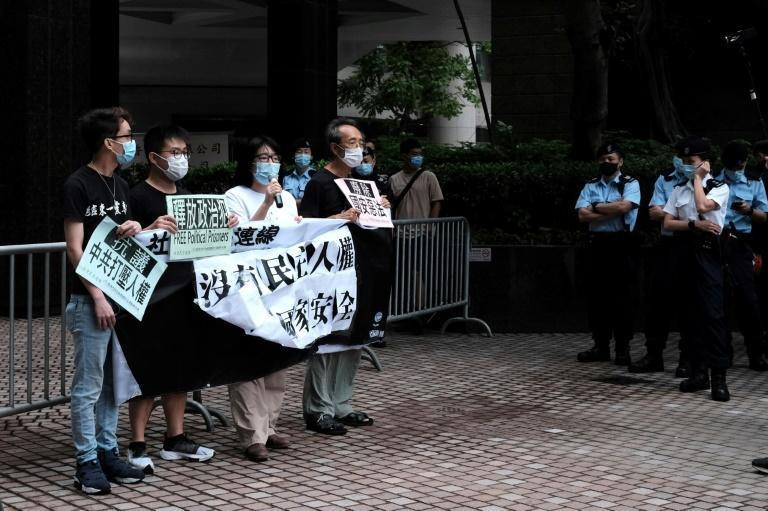 Four democracy activists held a lonely rally flanked by dozens of police officers