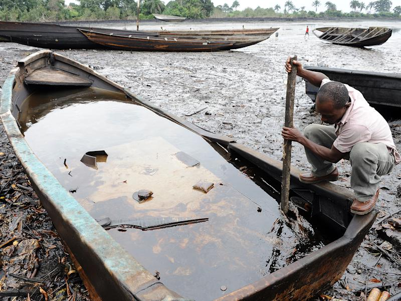 A man from the Bodo community, in Ogoniland, tries to separate with a stick the crude oil from water in a boat after waterways were polluted by oil spills attributed to Shell equipment failure: PIUS UTOMI EKPEI/AFP/Getty Images
