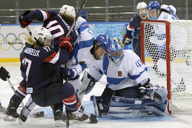 Goalkeeper Noora Raty of Finland reaches for the puck as Anna Kilponen of Finland (5) keeps Meghan Duggan of the Untied States (10) and Jocelyne Lamoureux of the Untied States (17) away from the gaoll during the third period of the women's ice hockey game at the Shayba Arena during the 2014 Winter Olympics, Saturday, Feb. 8, 2014, in Sochi, Russia. (AP Photo/Matt Slocum)