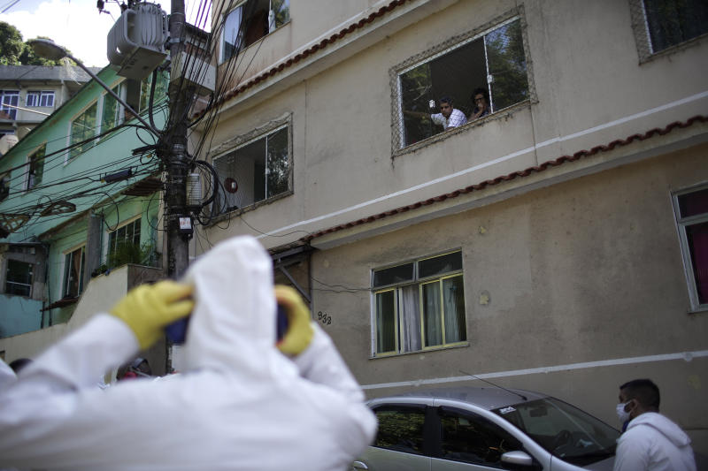 Residents watch water utility workers from CEDAE disinfecting the Vidigal favela in an effort to curb the spread of the new coronavirus, in Rio de Janeiro, Brazil, Friday, April 24, 2020. (AP Photo/Silvia Izquierdo)
