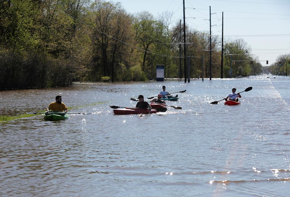 Residents paddle kayaks along a flooded street
