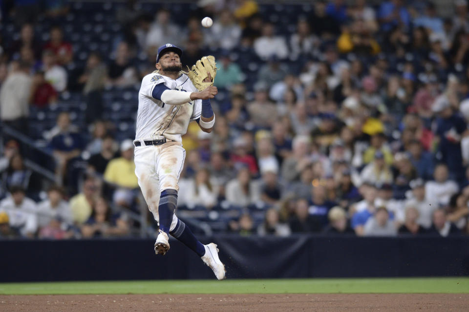 FILE - In this Aug. 8, 2019, file photo, San Diego Padres shortstop Fernando Tatis Jr. throws to first base late on a single by Colorado Rockies' Yonathan Daza during the sixth inning of a baseball game, in San Diego. Padres rookie shortstop Fernando Tatis Jr. has become one of major league baseballs most exciting young players, showing an instinct and aggressiveness that make it hard to believe hes only 20. (AP Photo/Orlando Ramirez, File)