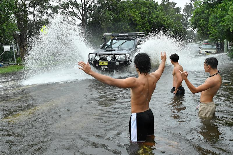A group of boys direct traffic through floodwater at Tempe in Sydney, Sunday, February 9, 2020.