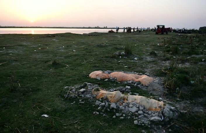 Bodies of suspected Covid-19 victims are seen in shallow graves buried in the sand near a cremation ground on the banks of the Ganges River in Unnao, India