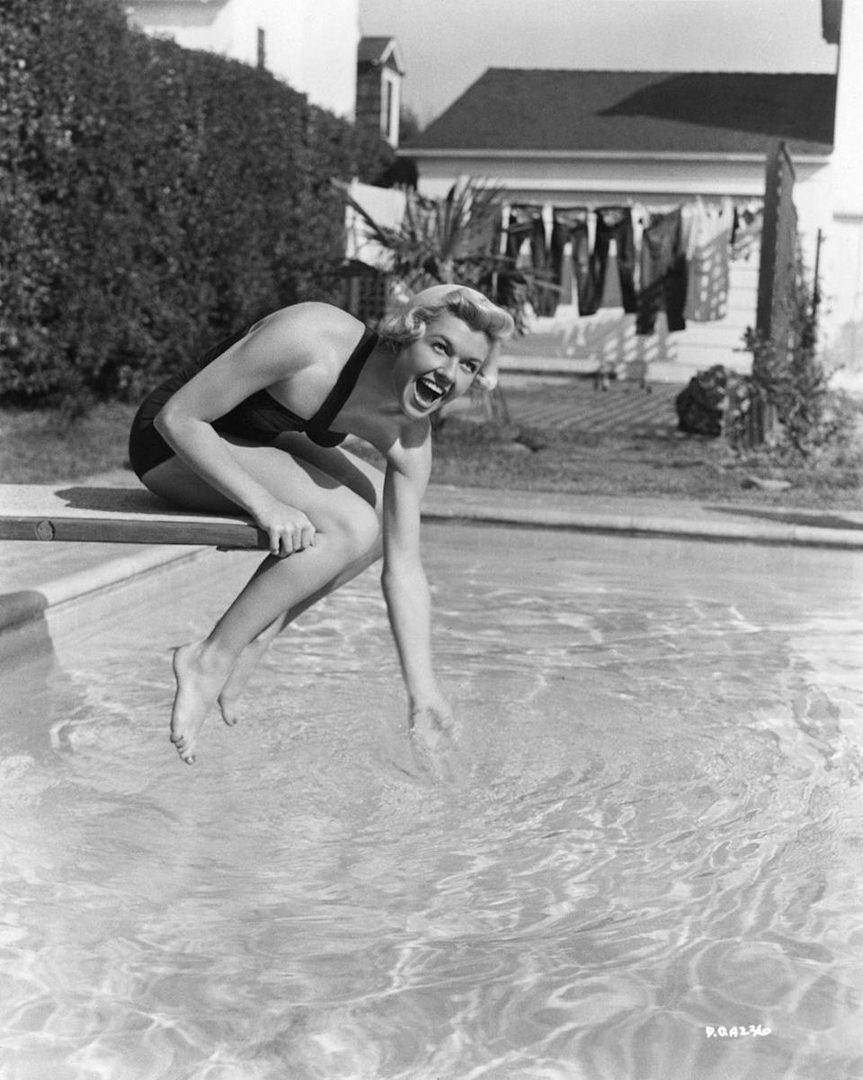 <p>Doris Day gets a feel for the water temperature before diving into her swimming pool in 1940. </p>