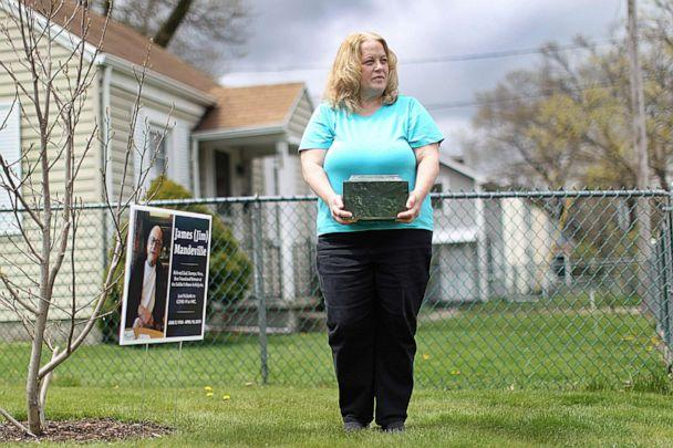 PHOTO: Laurie Beaudette holds the remains of her father, Jim Mandeville, who died April 14 at 83 of coronavirus after 16 years at Holyoke Soldiers' Home, on May 1, 2020 in Springfield, Mass. (Boston Globe via Getty Images, FILE)