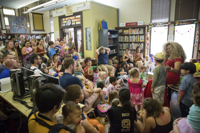 Vanessa Carr , right, reads to children during Drag Queen Story Time at the Alvar Library in New Orleans on Saturday, Aug. 25, 2018. Children and parents and caregivers packed into the library to hear drag queens Blazen Haven and Carr read stories and sing songs during the event. (Scott Threlkeld/The Advocate via AP)
