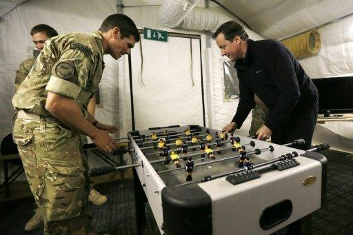 British Prime Minister David Cameron (R) plays table football in Helmand Province, Afghanistan, on December 20, 2012