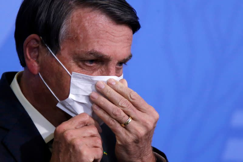 FILE PHOTO: Brazil's President Jair Bolsonaro looks on as he adjusts his protective face mask during a ceremony launching a program to expand access to credit at the Planalto Palace in Brasilia