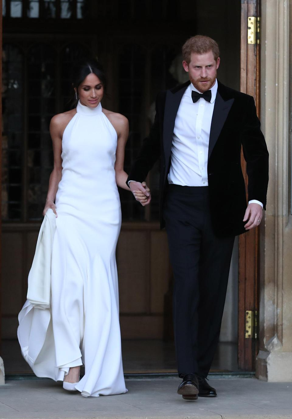<p>The newly-appointed Duchess of Sussex changed into a halterneck Stella McCartney gown for her evening reception. Teamed with a pair of Altuzarra heels (complete with a blue sole as her 'something blue') the former actress looked every inch the Hollywood icon. <em>[Photo: Getty]</em> </p>