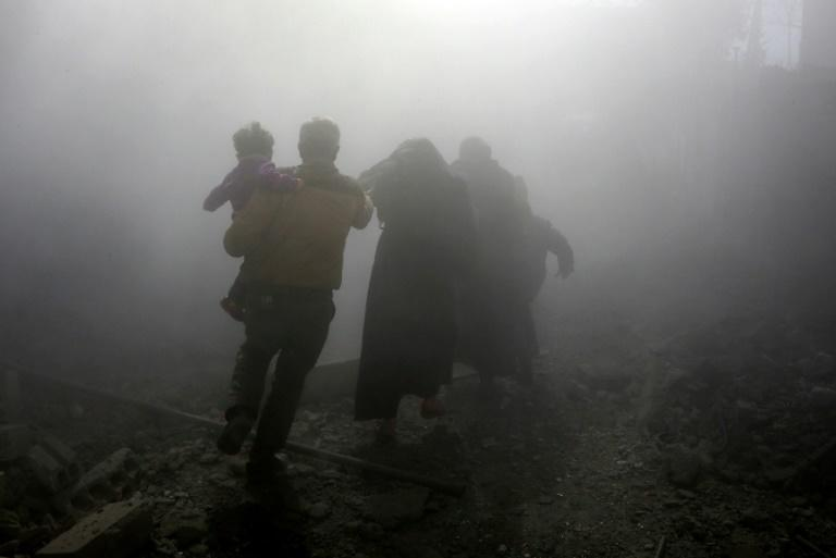 A family runs for cover through the dust cloud kicked by an air strike on the rebel-held Syrian town of Jisreen, on February 8, 2018