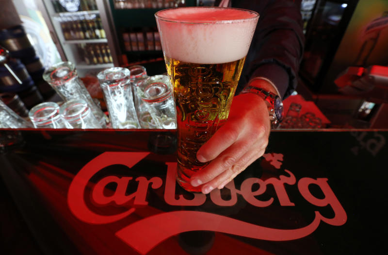 A bartender holds a glass of Carlsberg beer in a bar in St. Petersburg June 17, 2014. Denmark's Carlsberg will keep its breweries in Russia running regardless of empty capacity, despite other brewers closing plants as Western sanctions over Ukraine hamper an already faltering economy. To match Interview CARLSBERG-RUSSIA/ REUTERS/Alexander Demianchuk (RUSSIA - Tags: BUSINESS)
